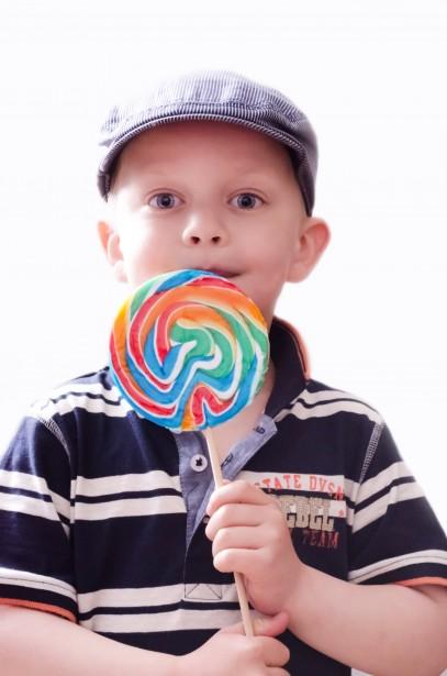 Un petit garçon avec un béret mange une sucette multicolore.